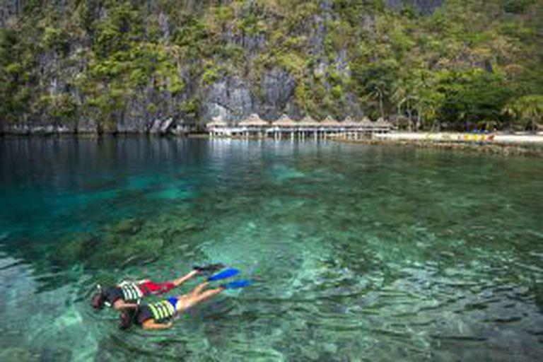 Banhistas praticam snorkel em frente a um resort em El Nido, nas Filipinas.