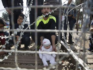 Homem e seu filho na fronteira entre a Grécia e a Macedônia, nesta terça-feira.