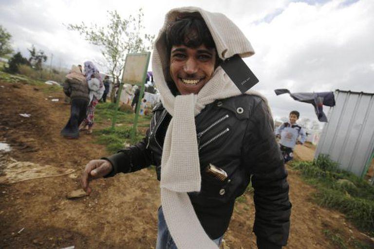 Homem sírio sorri para a câmera depois de receber roupa doada pela empresa espanhola Inditex, distribuída por grupos locais nos campos de refugiados de al-Bireh, ao norte de Trípoli, no Líbano.