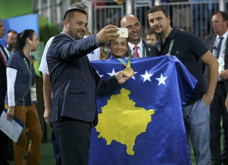 Majlinda Kelmendi, rodeada de aficionados, com a bandeira do Kosovo.