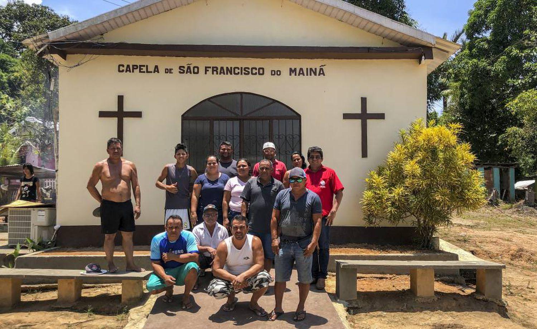 Da Silva (de azul no centro), com outros moradores em frente à capela da comunidade.