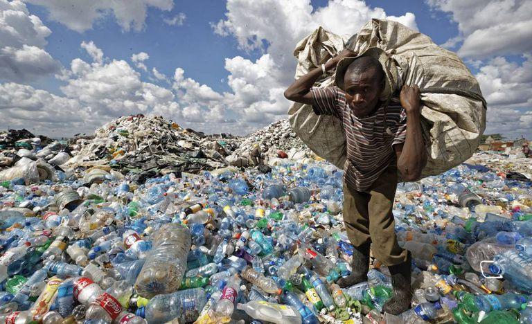 Homem enche uma sacola com plásticos em um lixão nos subúrbios de Nairóbi, Quênia.