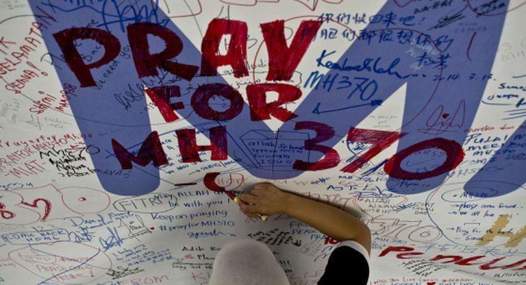 Um funcionário da Malaysia Airlines escreve uma mensagem no aeroporto de Kuala Lumpur.