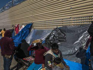 Um grupo de imigrantes aguarda em um acampamento improvisado diante do muro fronteiriço em San Luis Rio Colorado, no Estado de Sonora.