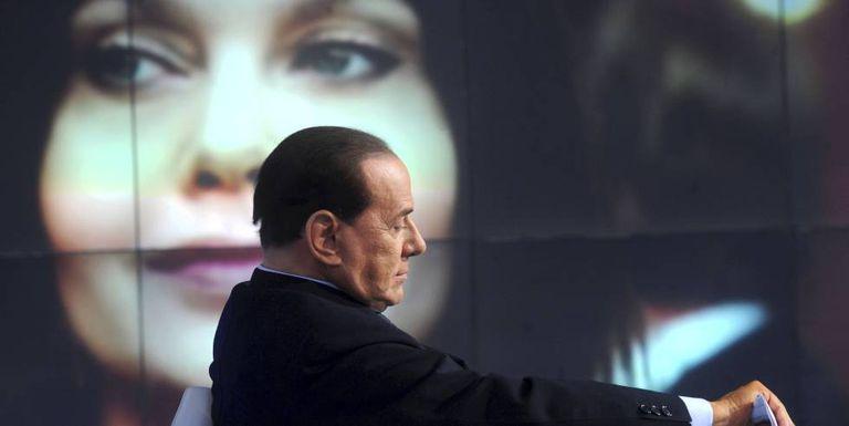 Silvio Berlusconi no primeiro plano, com sua ex-mulher Veronica Lario ao fundo da imagem