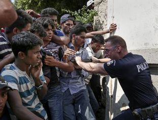 Um policial tenta conter centenas de imigrantes que pedem documentos, na segunda-feira em Kos.