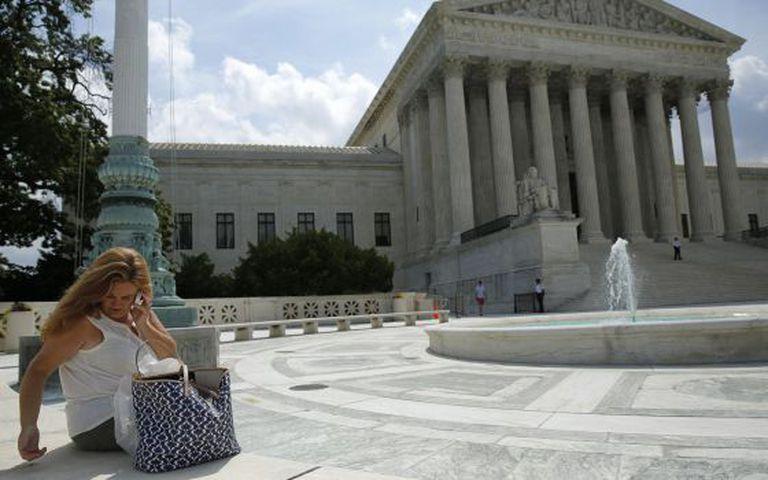 Uma mulher usa seu celular diante do Tribunal Supremo.