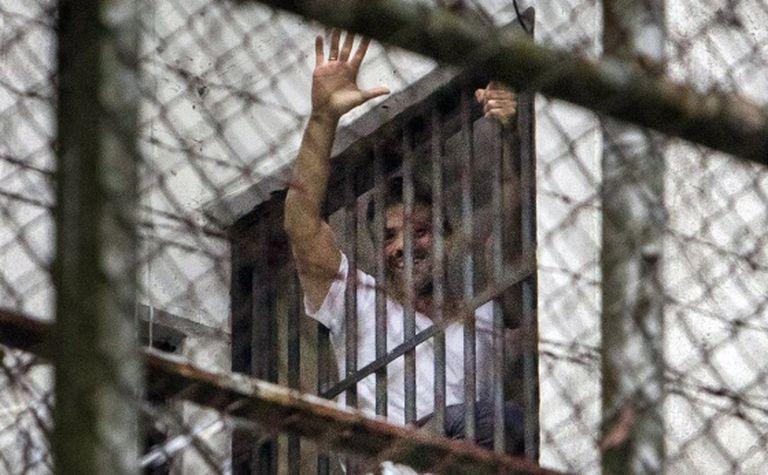 Leopoldo López acena de janela da prisão militar Ramo Verde, em Caracas.