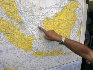 Um funcionário aponta no mapa o provável local do acidente.