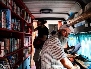 Ônibus-biblioteca foram instalados em Atenas para que os milhares de refugiados possam ler.