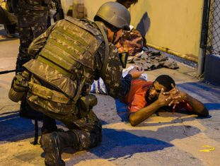 Soldados do exército revistam pessoas nesta segunda, em Vitória.