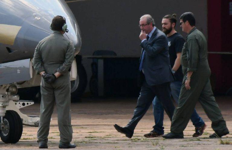 Preso, Eduardo Cunha é levado para avião da PF.