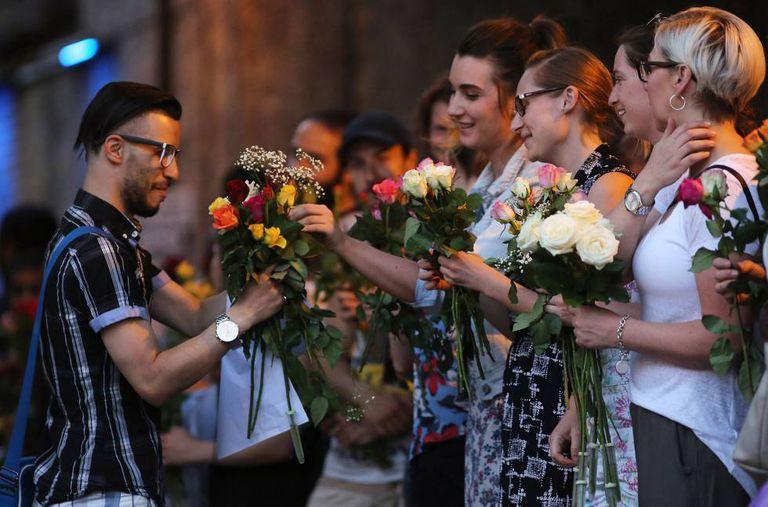 Mulheres dão flores a um homem que sai da mesquita de FInsbury Park.