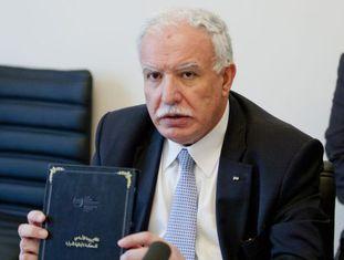 O ministro de Exteriores palestino, Riad al-Makli, com uma cópia do Estatuto de Roma.