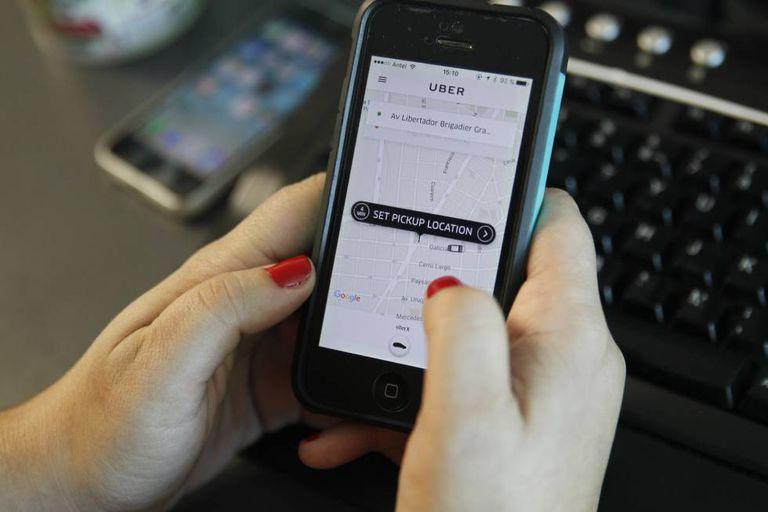 Uma pessoa pede um veículo através da aplicação móvel Uber.