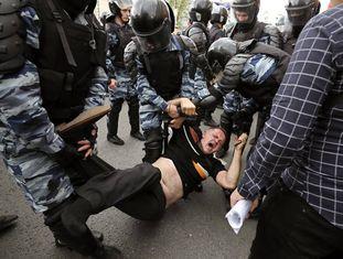Membros da polícia prendem um dos participantes da manifestação opositora em Moscou.