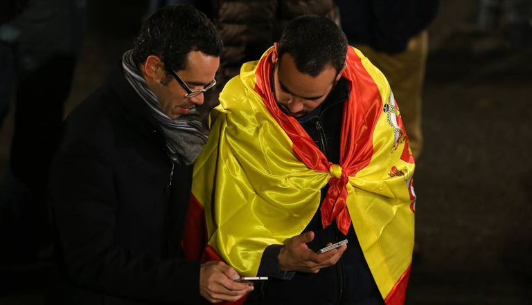 Duas pessoas esperam o resultado das eleições gerais espanholas de 2015.