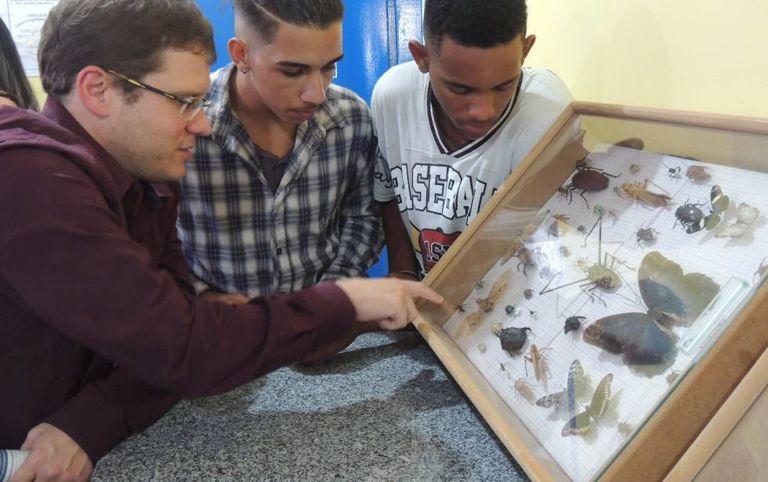 Rodrigo Fonseca, à esquerda, conversa com dois rapazes no laboratório.