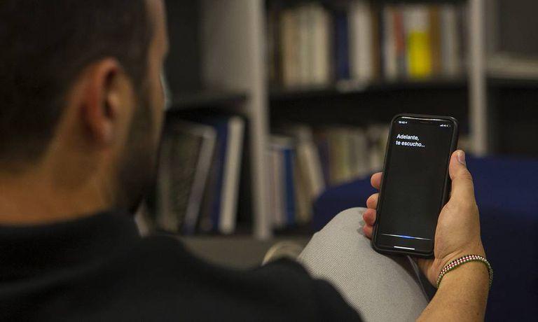 Um usuário de iPhone realiza uma consulta através da Siri.