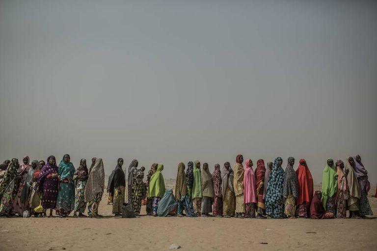 Mulheres refugiadas fazem fila em um campo de refugiados para receber um kit de higiene.