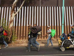Migrantes centro-americanos caminham nesta terça-feira em Mexicali (México) ao lado da cerca na fronteira com os EUA.