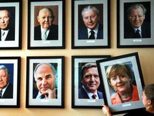 Uma mulher pendura um retrato de Merkel cinco anos atrás.