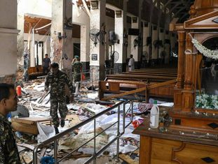EDITORS NOTE: Graphic content / Sri Lankan security personnel walk past dead bodies covered with blankets amid blast debris at St. Anthony's Shrine following an explosion in the church in Kochchikade in Colombo on April 21, 2019. - A string of blasts ripped through high-end hotels and churches holding Easter services in Sri Lanka on April 21, killing at least 156 people, including 35 foreigners. (Photo by ISHARA Séc. KODIKARA / AFP)