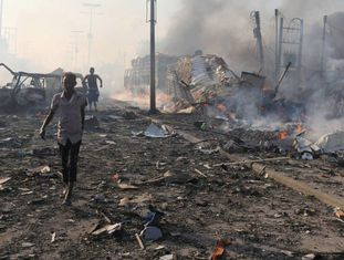 Mogadício, capital da Somália, foi alvo de um ataque terrorista no sábado que deixou mais de 300 mortos. A falta de atendimento adequado às vítimas agrava a situação de um país cuja história é ligada à guerra, ao terrorismo do Al Shabab, à pirataria no Oceano Índico e à seca extrema que faz com que 6,7 milhões de pessoas, metade do país, precisem de ajuda humanitária urgente. Dessas, 275.000 crianças sofrem de desnutrição aguda severa, o estado mais perigoso, aquele que as coloca à beira da morte. A ONG Save the Children atende essas crianças e suas famílias em hospitais e em campos de refugiados. Se a situação não melhorar, o país enfrentará sua terceira declaração de estado de fome, após a de 1992 e a de 2011 que deixaram milhares de vítimas. Na foto, civis deixam área de atentado em Mogadíscio, a capital da Somália, em que aos menos 302 já morreram. Dezenas ainda buscam parentes desaparecidos após o ataque do sábado. Caos no atendimento dos feridos é só uma faceta das agruras em que o país está mergulhado, com a volta com força da pirataria, o terrorismo e seca e a fome aguda