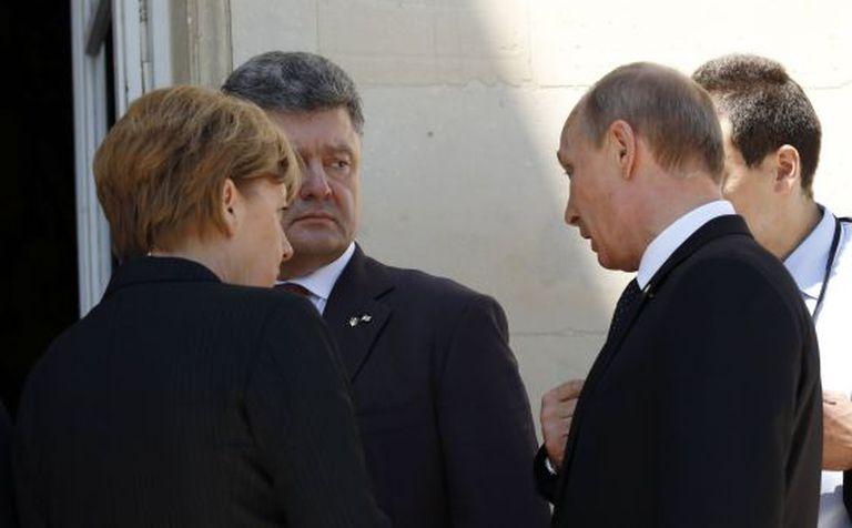 Putin e Poroshenko conversam diante de Angela Merkel.