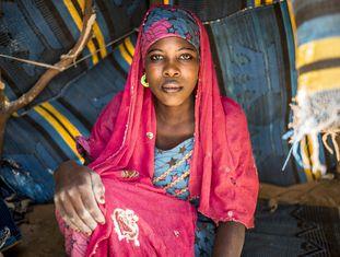 """Mariama, da etnia kanuri, é uma das jovens fugitivas da violência do Boko Haram na aldeia de Goumseri Argou, perto da fronteira entre o Níger e a Nigéria. Agora ela vive a poucos metros da estrada Nacional 1, do lado nigerino, em um pequeno abrigo feito de palha e tapetes. """"Não quero voltar, o Boko Haram estava a uma distância muito pequena e tivemos problemas constantes com eles, eu tenho medo que me sequestrem como já aconteceu com tantas jovens nigerianas"""", afirma. À noite, muitos dos novos deslocados vão dormir longe dos assentamentos porque ainda temem os ataques. Para fazer fogo para se aquecer ou cozinhar, e para construir seus abrigos, cortaram galhos das árvores próximas."""
