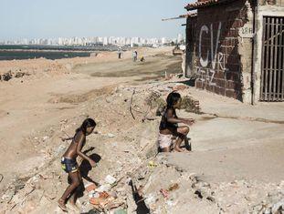 Crianças brincam em praia no Pirambu. Ao fundo, pichação do Comando Vermelho.