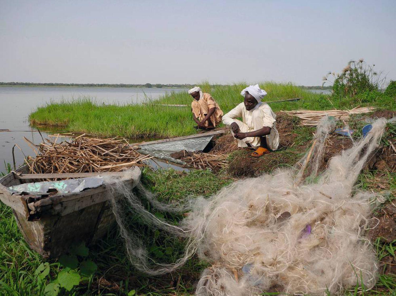 Dois pescadores trabalham em uma ilhota do lago Chad. Em meio século, as secas reduziram em mais de 90% esta grande massa de água.