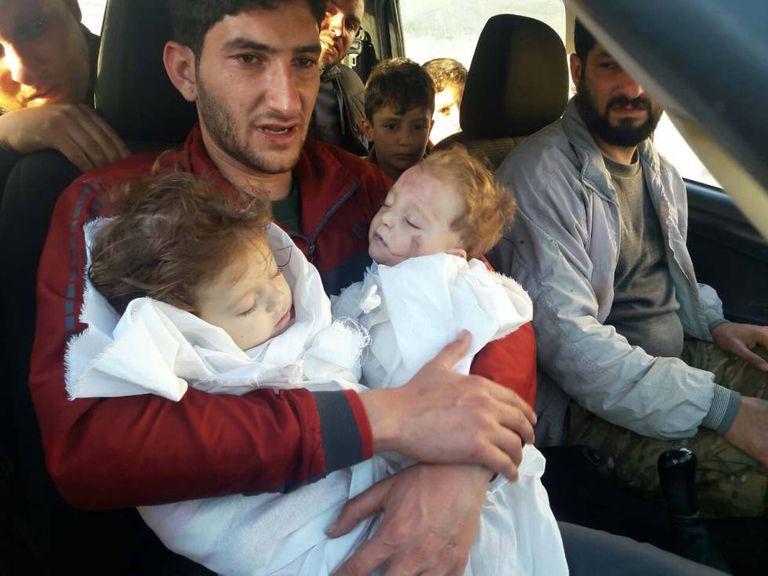 Hassan Youssef,, com os cadáveres de seus dois filhos mortos no ataque de gás tóxico na Síria.