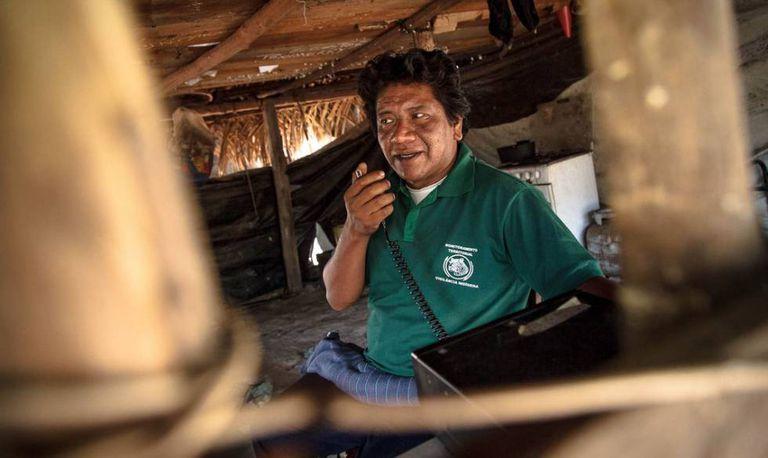 A liderança indígena Dototakakyre Kayapó (conhecido como Dotô) utilizando o rádio. Foi através da comunicação entre aldeias que os indígenas mapearam as áreas onde a quadrilha de grilagem atuava.