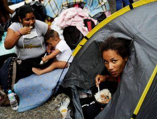 Mulher almoça no acampamento montado para receber moradores de prédio que caiu, em São Paulo.