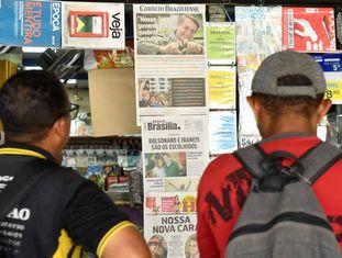 Homens leem as manchetes em banca de jornal de Brasília.
