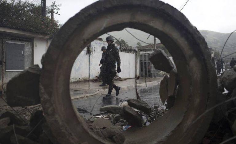 Soldados passam por barricada durante operação surpresa na favela da Coreia, no Rio de Janeiro.