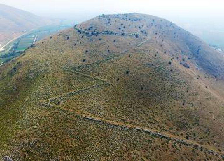 Os vestígios das muralhas serpenteiam a colina.