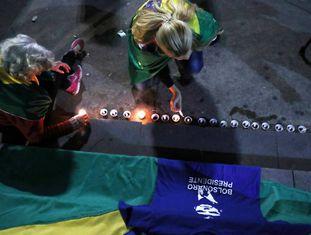 Mulher acende vela por presidenciável Jair Bolsonaro