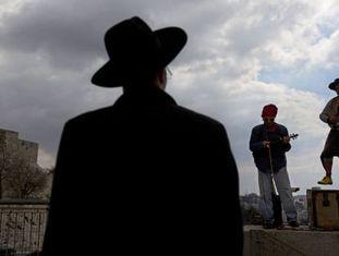 Um judeu ultraortodoxo observa uma apresentação musical em Jerusalém.
