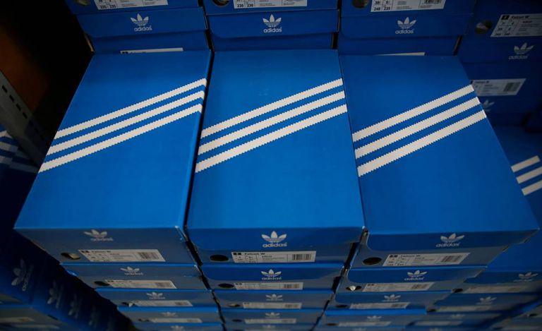 Pilha de caixas de tênis Adidas com o desenho das três listras.