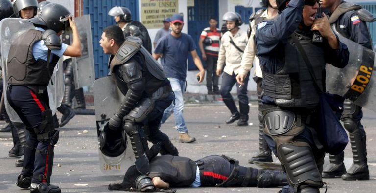 Policial fica caído após ser atropelado durante os protestos.