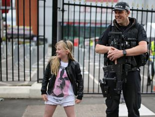 Menina posa com um policial antes do show de Ariana Grande em Manchester, neste domingo.