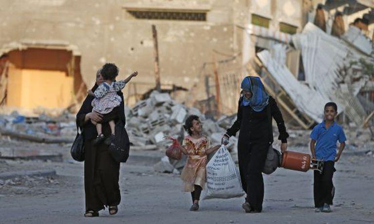 Palestinos caminham para um abrigo da ONU, em Gaza.