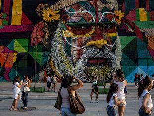 Pessoas caminham pela orla do porto, em frente ao grafite do artista Eduardo Kobra.