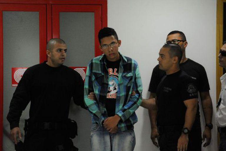 O suspeito Caio Silva de Souza (centro) na sede da polícia do Rio.