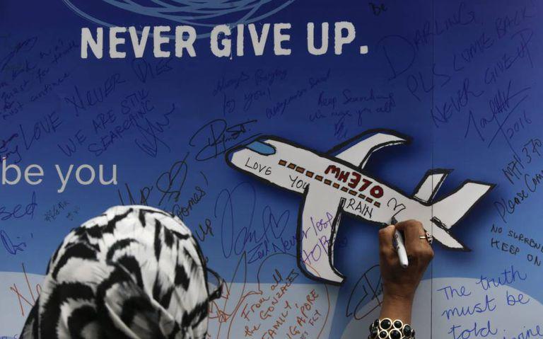 Mulher deixa uma mensagem em um memorial das vítimas do voo MH 370 em Kuala Lumpur, na Malásia, em março de 2016.
