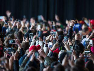Uma multidão fotografa um ato com seu móvel.