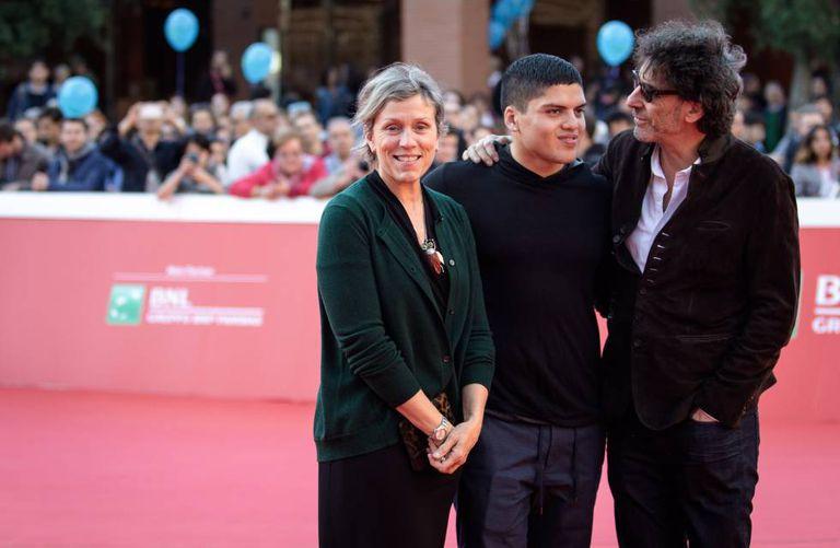 Com seu marido, Joel Coen (à direita), e seu filho, Pedro.