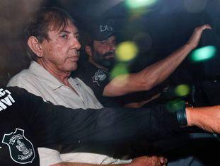 João de Deus escoltado pela polícia para cumprir a ordem de prisão.